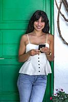 Positive Hispanic female in casual clothes smiling and looking at camera while leaning on green door and browsing smartphone outside house.