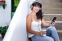 Cheerful ethnic lady with takeaway cup of hot drink smiling for camera and browsing smartphone while resting on steps and listening to music.