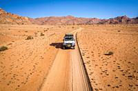 A lone jeep on an expedition across the desert , Helmeringhausen, Namibia.