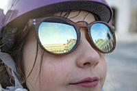 Little girl wearing mirror sunglasses at Upper Square of Badajoz. She is looking to the sky.