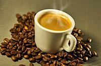 Hot espresso coffee between coffee beans.