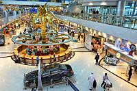 Elevated view of the luxurious duty-free shop at Dubai International Airport with a stall selling golden jewelry by weight in the center. Dubai, UAE.