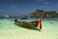 Traditional long-tail Thai boat moored at the Monkey beach on Phi Phi Don island. Ko Phi Phi archipelago, Thailand.