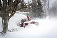 snowblower blowing snow from driveway during blizzard, Meaford, Ontario, Canada.