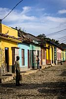 Man standing in a typical cobblestoned street with colourful houses in the colonial era centre of the town, Trinidad, Cuba.