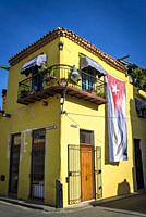 Huge Cuban flag hanging on the building in the Old City Centre, Havana Vieja, Havana, Cuba.