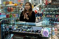 A young woman is praying at her work place as a watch seller In a mall in Siam Square, Bangkok. Thailand