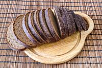 Sliced loaf of rye bread on a cutting board close up.