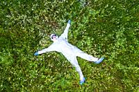 Person with a safety suit lying down in a flowers carpet in a forest area. Ayegui, Navarre, Spain, Europe.