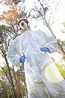 Person with a safety suit in a forest area. Ayegui, Navarre, Spain, Europe.