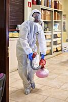 Worker in protective suit disinfect interior office.