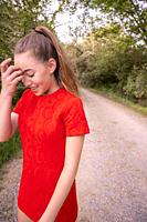 A 14 year old brunette girl with a hand to her face wearing a short red dress on a dirt country road.