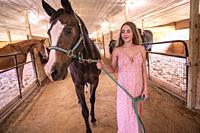A 14 year old brunette girl leading her horse through a stable.