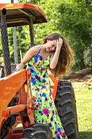 A laughing 14 year old brunette girl wearing a long colorful dress standing on a tractor.