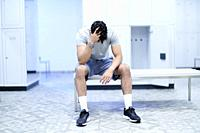 Tired man sitting in gym locker room