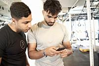 Two men looking at smart phone in gym