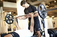 Personal trainer assisting man lifting weights in gym