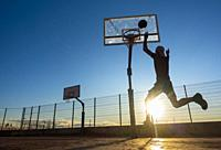 Mature man playing Basketball on outdoor court at sunrise in Las Palmas, Gran Canaria, Canary Islands, Spain. Model released.