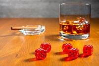Red dice on a wooden table. Glass of whiskey with ice cubes and an ashtray with a cigar in the background.