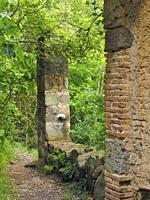 Entrance door of mill room. Antique ruins at Mir cascade site. Santa Maria de Besora village countryside. Osona region, Barcelona province, Catalonia,...