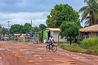 Local cyclist riding along muddy dirt road in the village Lethem during the rainy season, Upper Takutu-Upper Essequibo region, Guyana, South America