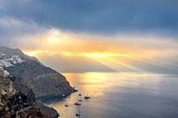 Greece. Heavy clouds over the caldera of Santorini. Sun Rays illuminates the bay and several anchored yachts.