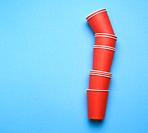 stack of red paper disposable cups on a blue background, flat lay, concept eco-friendly, zero waste.
