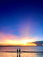 Two people silhouette on Mindil beach, Darwin Australia, during sunset.