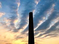 Tall chimney against sun rise