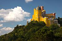 Portugal. Sintra. The Pena Palace on a cliff surrounded by forest and clouds.