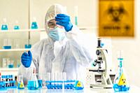 Scientists hold test tube and examine for his research and develop vaccine for coronavirus covid-19 pandemic in Laboratory room with caution signage. ...