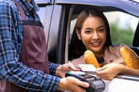 Portrait of asian woman make mobile payment contactless technology for online grocery ordering and drive thru service. Drive through and food online i...