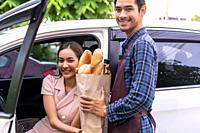 Delivery staff giving grocery bag set to asian customer woman at drive thru service station of Supermarket. Drive thru is popular service and new norm...