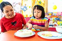 Asian girl kid cutting her birthday cake celebrate with mom alone because city lockdown while COVID-19 Pandemic. Celbration and quarantine concept.