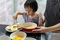 Asian girl cooking egg tart bakery with her mom, housework for child make executive function for kid. Houseworking food lifstyle and family concept.