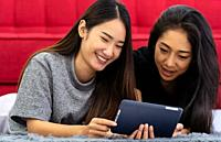 Two Asian women sister smiling and happy from using tablet in living room to video call to their friends while city lockdown from COVID-19 Pandemic. L...