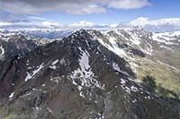 aerial shot, from a sailplane, of western ridge and peaks on Gavia high mountain valley, shot in Alps in bright late springtime light, Sondrio, Lombar...