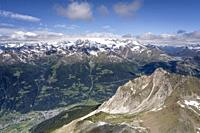 aerial shot, from a sailplane, of Sperella peak rocky summit with Poschiavo valley and Bernina range and lake in background , shot in Alps bright late...