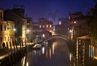 Dusk among mists on a canal in Venice, with the Church of Santa Maria del Rosario in the background.