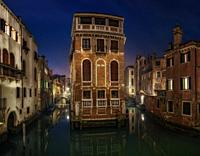 A Venice house between canals at sunrise.