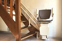 Automatic stairlift on staircase for elderly or disability in a house, taking people up and down.