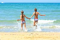 Children holding hands run swimming in the sea.