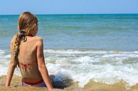 A girl sits on a sandy sea beach and looks into the distance.
