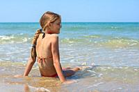 A girl of ten years old sits in the water on the sea coast.