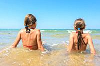 Children sit in the water on the coast and look into the distance.