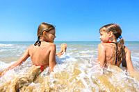 Children sit in water on a sandy beach and look at each other happily.