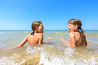 Children sit together in shallow water and show each other tongue.