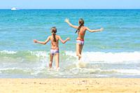 Cheerful children run to swim in the sea.