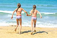 Two little sisters running to swim in the sea, back visas.