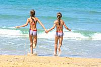 Girls holding hands run into the sea.